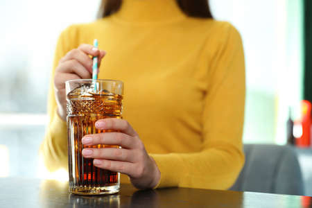 Woman with glass of refreshing cola at table indoors, closeup. Space for text