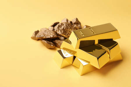 Gold nuggets and ingots on color background