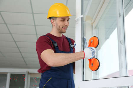 Trabajador de la construcción con elevador de succión durante la instalación de ventanas en interiores Foto de archivo