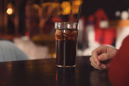 Man with glass of refreshing cola at table indoors, closeup. Space for text