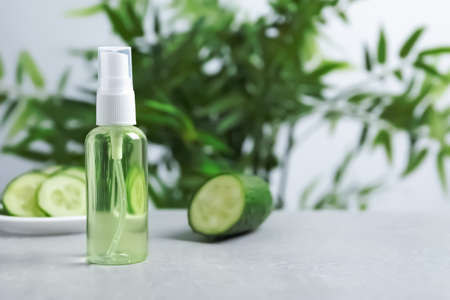 Cucumber tonic in bottle on table against blurred background. Space for text