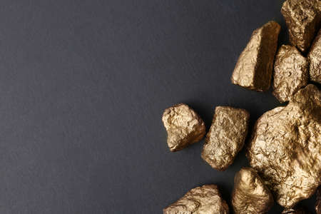 Pile of gold nuggets on dark background, flat lay with space for text Stock Photo