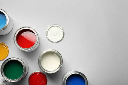 Open paint cans and space for text on grey background, top view Stock Photo