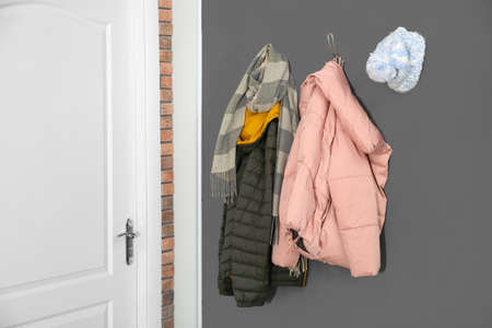 Different clothes hanging on grey wall near door. Hallway interior elements