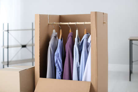 Wardrobe box with clothes on hangers indoors Stock Photo