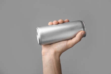 Man holding aluminum can with beverage on grey background, closeup. Space for design