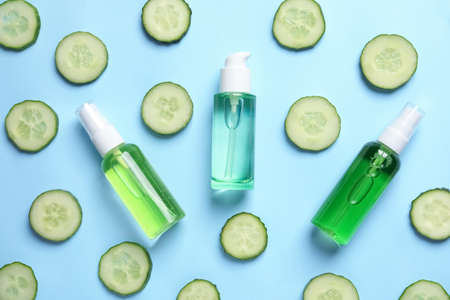 Flat lay composition with fresh cucumber slices cosmetic bottles on color background Фото со стока