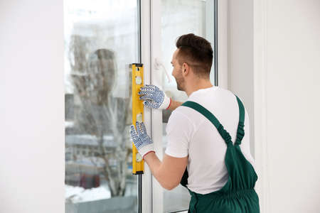 Construction worker using bubble level while installing window indoors Stock Photo