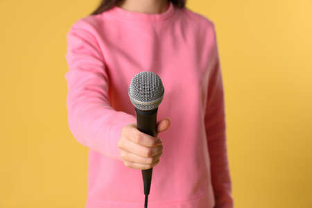 Young woman holding microphone on color background, closeup view