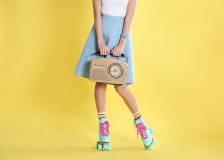 Young woman with roller skates and retro radio on color background, closeup