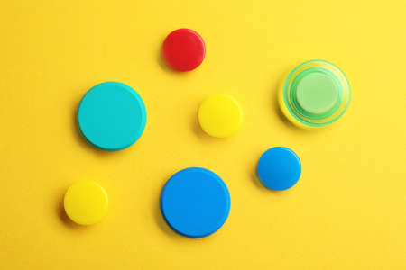 Bright magnets on color background, top view