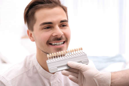 Dentist checking young man's teeth color in dental office