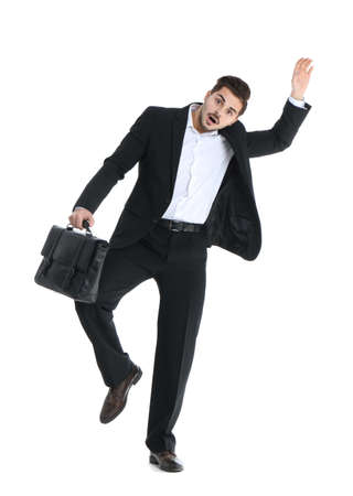 Young businessman attracted to magnet on white background
