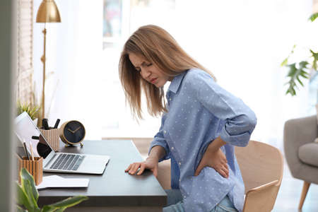 Young woman suffering from back pain in office