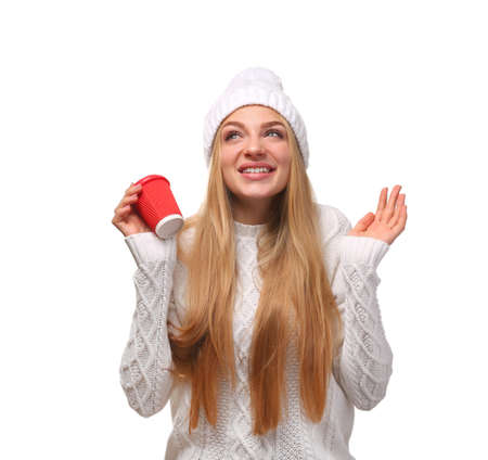 Portrait of young woman in stylish hat and sweater with coffee paper cup on white background. Winter atmosphere Stock Photo