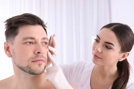 Doctor examining patient in clinic. Visiting dermatologist Stock Photo