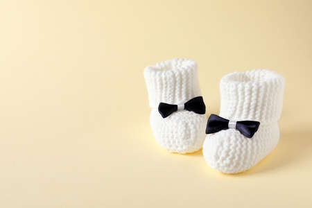 Handmade baby booties on color background. Space for text