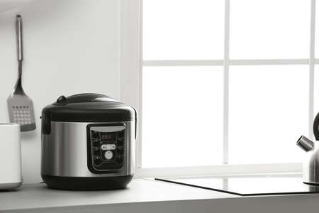Modern electric multi cooker on kitchen countertop. Space for text Stock Photo
