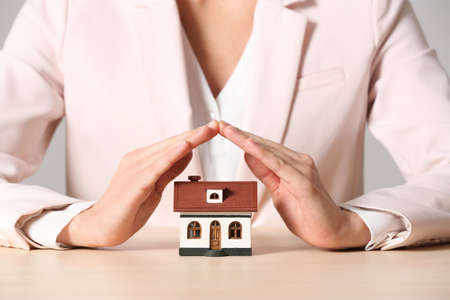 Female agent covering house model at table, closeup. Home insurance