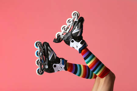 Woman with roller skates on color background, closeup 免版税图像