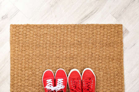 New clean doormat with shoes on floor, top view. Space for text Imagens