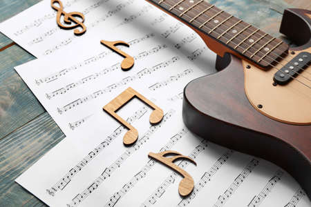 Guitar and sheets with music notes on wooden table