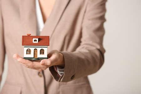 Female agent holding house model on light background, closeup. Home insurance