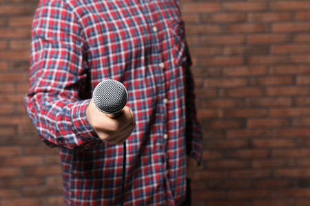 Young man in shirt holding microphone near brick wall, closeup with space for text