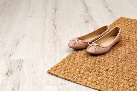 Nuevo felpudo limpio con zapatos en el piso. Espacio para texto Foto de archivo