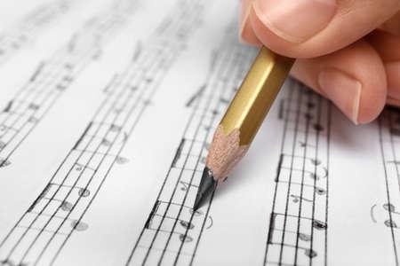 Mujer escribiendo notas musicales en la hoja con lápiz, primer plano Foto de archivo