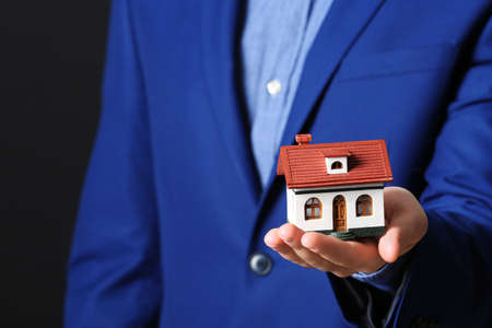 Male agent holding house model on black background, closeup. Home insurance
