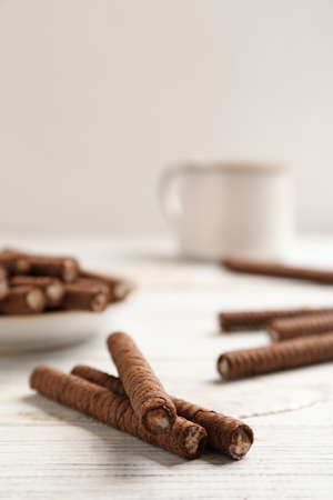 Delicious chocolate wafer rolls on white wooden table, space for text. Sweet food