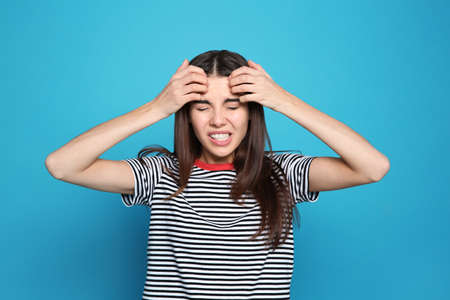 Young woman scratching head on color background. Annoying itch Stock Photo