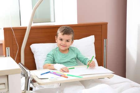 Niño con dibujo de goteo intravenoso en la cama de un hospital