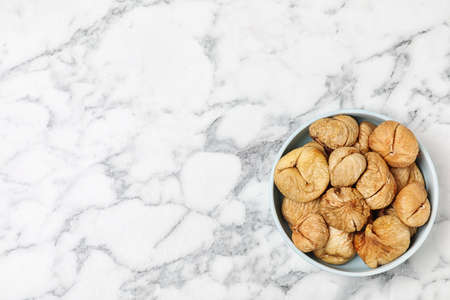 Bowl of dried figs on marble table, top view with space for text. Healthy fruit Archivio Fotografico