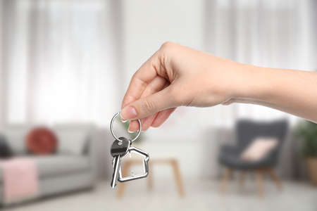 Woman holding house key in modern living room, closeup