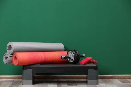 Set of fitness equipment on floor near color wall. Space for text