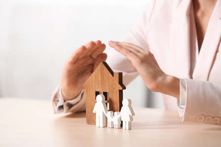 Female agent covering wooden house and family at table, closeup. Home insurance Reklamní fotografie