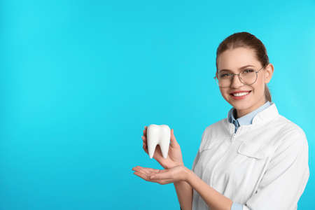 Female dentist holding tooth model on color background. Space for text Stockfoto