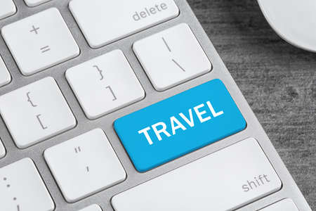 Computer keyboard with  button and word Travel. Tourist agency