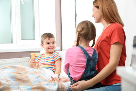 Happy family visiting little child in hospital Stock Photo