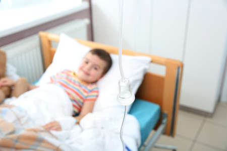 Little child with intravenous infusion in hospital bed, focus on drip chamber