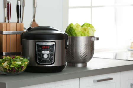 Cocina multiuso eléctrica moderna y comida en la encimera de la cocina. Espacio para texto