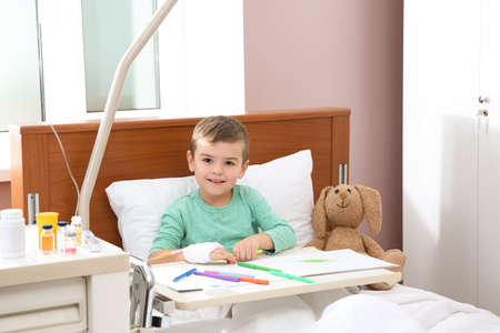 Little child with intravenous drip drawing in hospital bed Archivio Fotografico