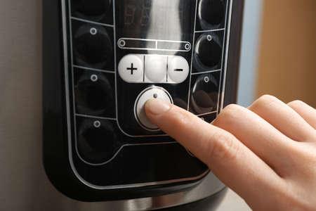 Woman turning on modern electric multi cooker, closeup