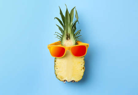 Funny pineapple with orange sunglasses on blue background, top view Banco de Imagens