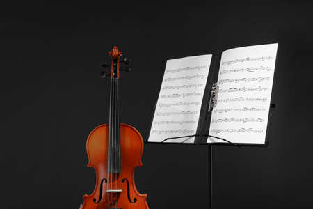 Violin and note stand with music sheets on black background