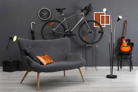 Stylish room interior with bicycle and orange elements Фото со стока