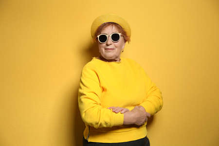 Portrait of elderly woman in hipster outfit on color background