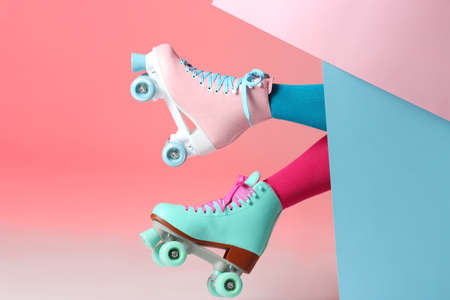 Woman with vintage roller skates on color background, closeup